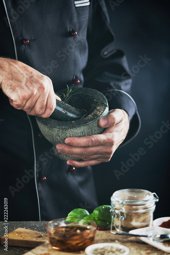 Male chef blending herbs in a mortar and pestle
