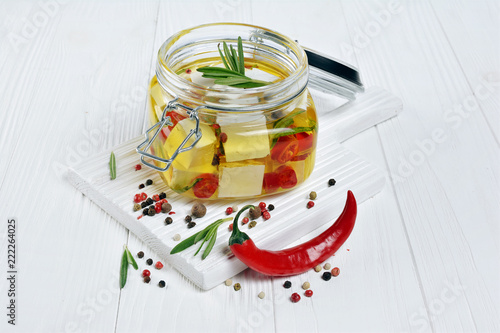 Marinated feta cheese with olive oil and spice of red chili pepper and rosemary in glass jar