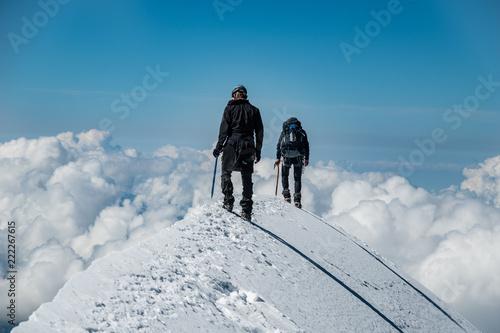 Obraz na plátně Alpinists on Aiguille de Bionnassay summit - extremely narrow snow ridge above c