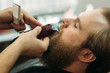 Bearded man getting a haircut by a professional hairdresser using comb and grooming scissors. Closeup view with shallow depth of field