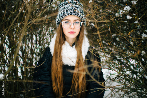 Fotografie, Obraz  Mood dramatic winter lifestyle outdoor portrait of young amazing girl in wool stylish hat and glasses looking deep at camera