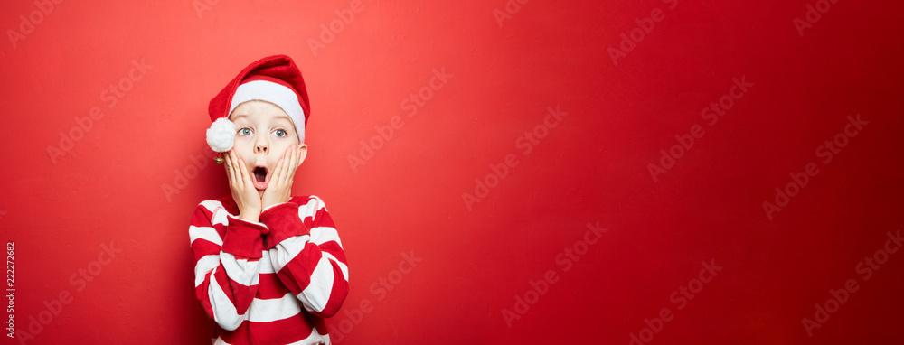 Fototapeta Junge zu Weihnachten vor einem roten Hintergrund