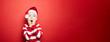 Leinwanddruck Bild - Junge zu Weihnachten vor einem roten Hintergrund