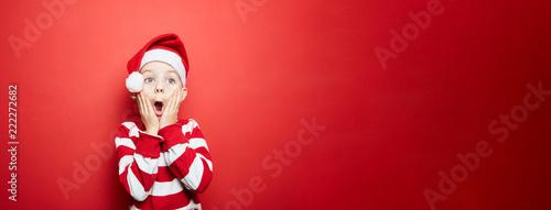 Fotografija Junge zu Weihnachten vor einem roten Hintergrund