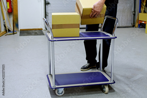 Fotografie, Obraz  Man collects cardboard boxes to material handling trolley in warehouse
