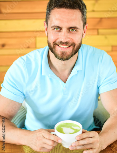 Photo  Man bearded guy drinks cappuccino at wooden table cafe