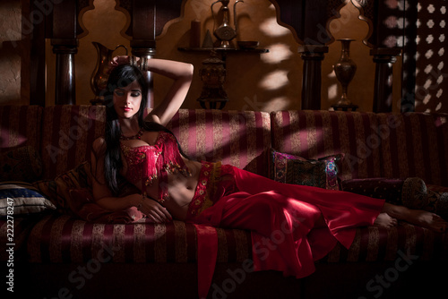 A girl in oriental attire in a dark room in the rays of light. Fototapet