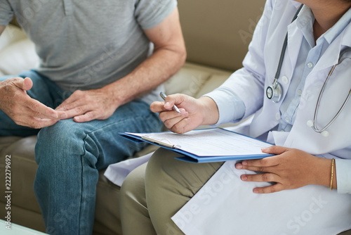 Leinwand Poster Crop shot of senior man sitting on sofa with doctor during home visit taking not
