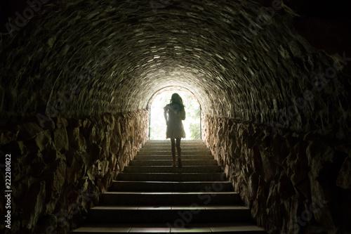Photographie Girl walking throug dark tunnel into light