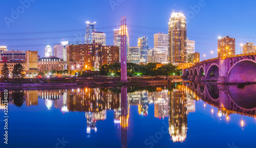 Photo Stands United States Minneapolis skyline with reflection in river at night.