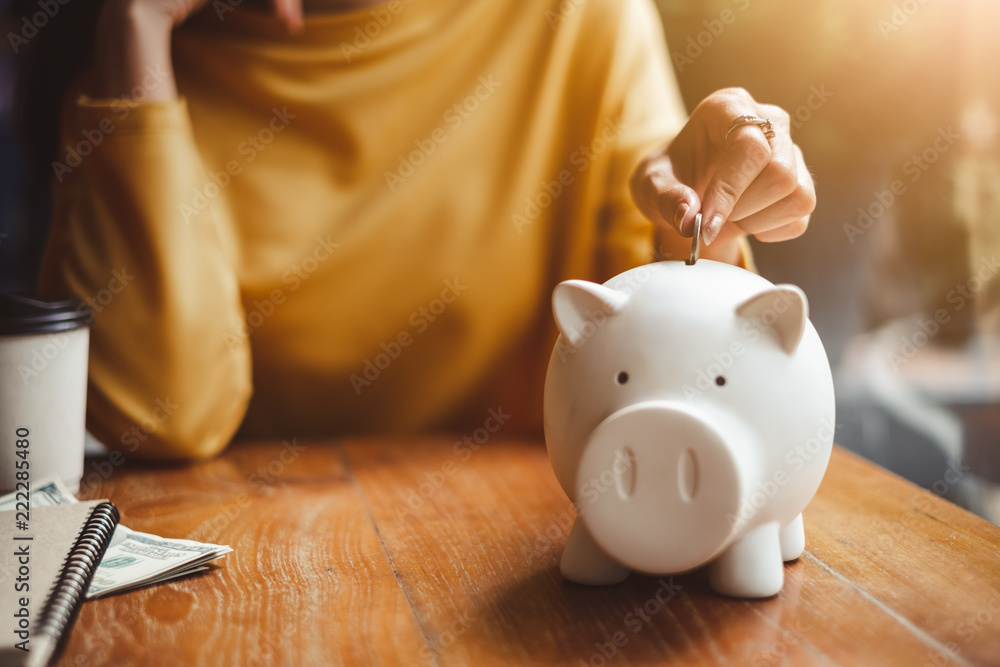 Obraz woman hand putting money coin into piggy for saving money wealth and financial concept. fototapeta, plakat