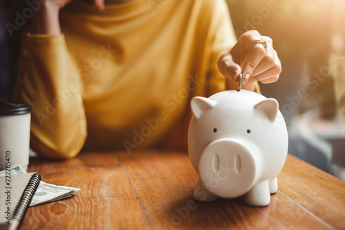 Fotografía  woman hand putting money coin into piggy for saving money wealth and financial concept