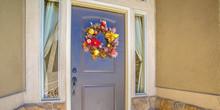 Blue Front Door With Flower Wreath Between Windows