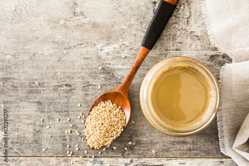 Photo Tahini and sesame seeds on wooden table. Top view. Copyspace
