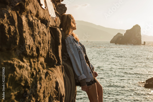 Young blond woman observing the horizon in an island in a sunset of summer