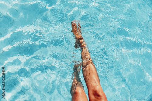 beautiful woman legs splashing in the pool