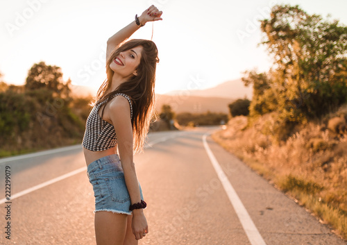 Young girl with hair bun and denim shorts dancing walking and smiling on the edge of the roadway in a sunset of summer