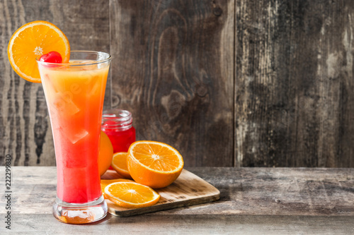 Tequila sunrise cocktail in glass on wooden table. Copyspace