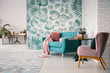canvas print picture - Chair and turquoise sofa in green living room interior with leaves wallpaper and table. Real photo