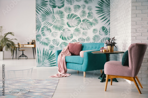 Chair and turquoise sofa in green living room interior with leaves wallpaper and table. Real photo - fototapety na wymiar