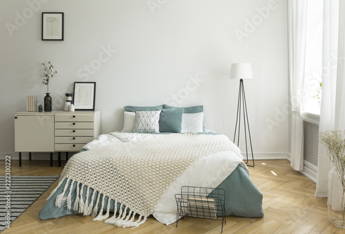 Fotografía  A big comfortable bed with pale sage green and white linen, pillows and blanket in a woman's bright bedroom interior with windows