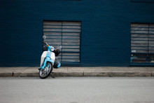 Blue Scooter Parked In Front Of A Blue Wall