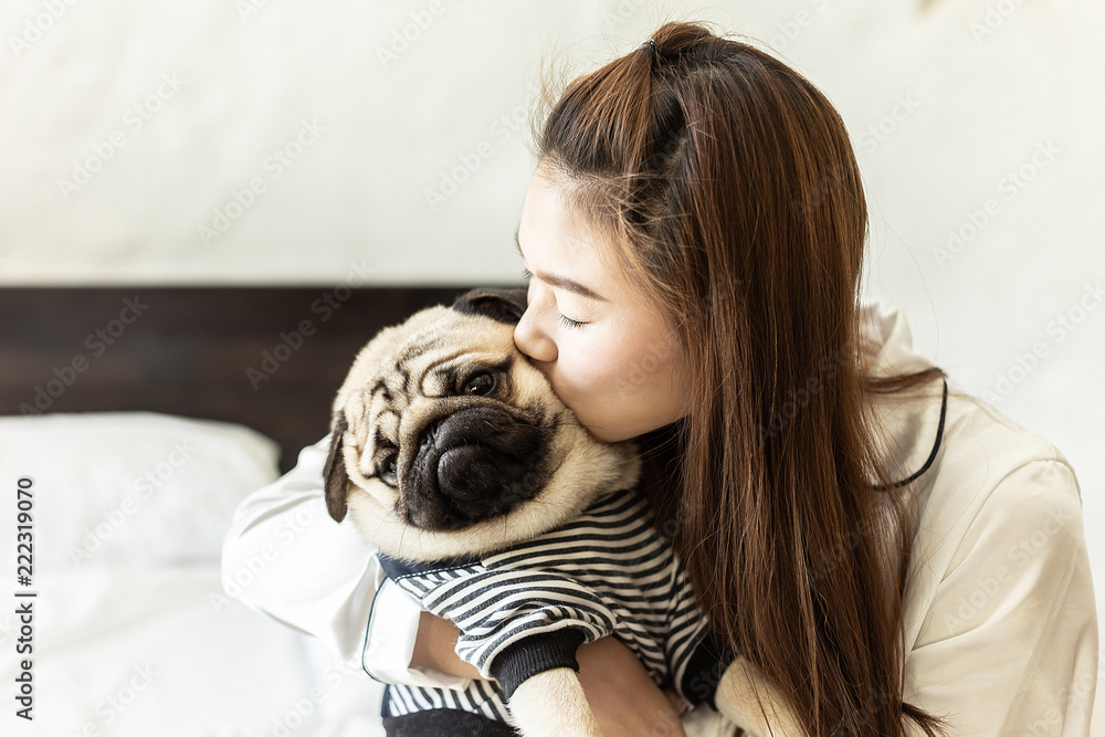 Fototapety, obrazy: Beautiful Attractive Asian woman kissing her Cute dog pug breed sleeping on bed feeling so sweet and lovely,Friendship Concept