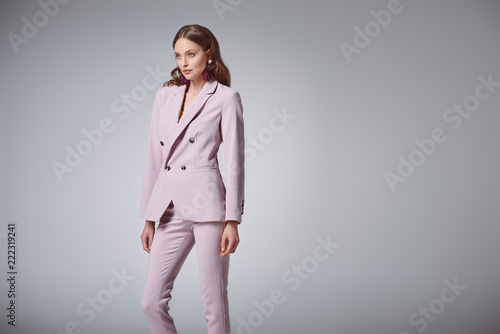 Fotografia attractive woman in fashionable pink suit looking away isolated on grey