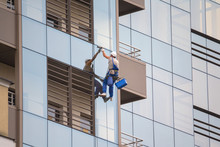 Industrial Climber Wash The Windows Of Modern Skyscraper. Professions