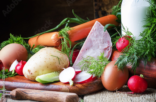 Ingredients for cold soup with vegetables, herbs and meat products, old wooden table, selective focus