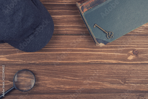 Fotomural Cap of a detective, a magnifying glass and an old book with a key on the book ag