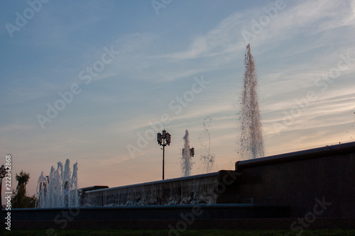 Fotografia  Evening picture - splashes of a fountain, a lantern and a very beautiful sky at sunset