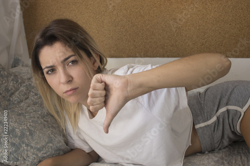 Fotografie, Obraz  young girl in bed gesturing thumbs down