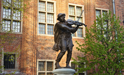 Fountain sculpture of musician in old town of the city, sunny day, Torun, Poland