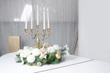 New Year's decorations and a golden candlestick with burning candles stand on the surface of a white grand piano