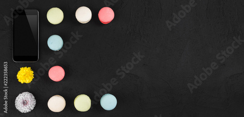 Tasty colorful macarons with phone and flowers on vintage stone background. Top view with copy space on the right