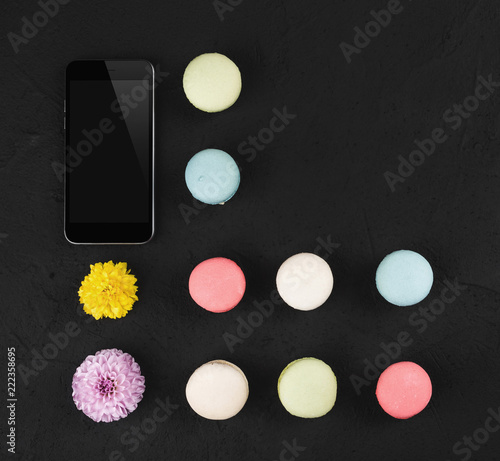 Blank screen phone mock-up, macarons and flowers on black background. Space for you text, top view