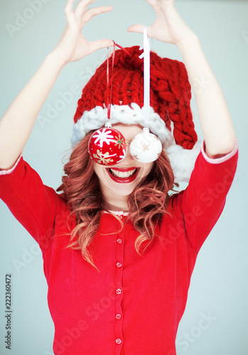 Fotografía  Beautiful happy young woman in a santa claus costume with perfect make up, red l