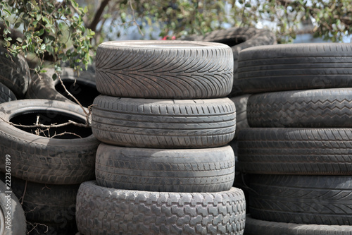 Fotografía  close up of a pile of used black dusty tires, outdoors, on street in the Gambia,