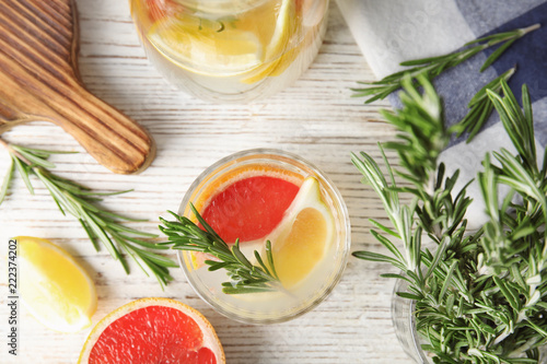 Flat lay composition with grapefruit and rosemary cocktail on light table