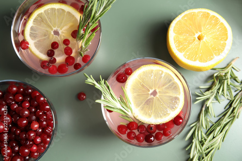 Flat lay composition with cranberry and rosemary cocktail on color table