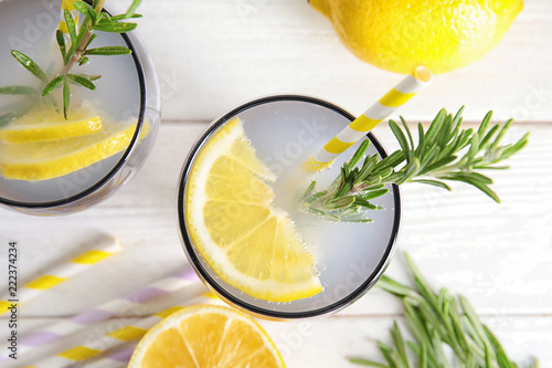 Flat lay composition with lemon and rosemary cocktail on light table