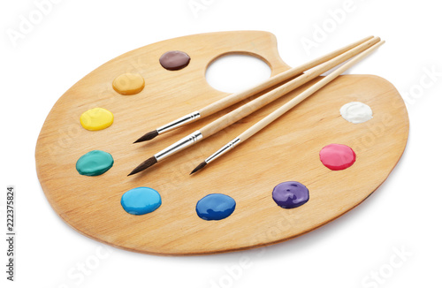 Palette with paints and brushes on white background