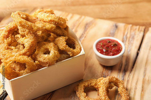 Cardboard box with crunchy fried onion rings and tomato sauce on wooden board