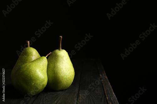 Ripe pears on wooden table against dark background. Space for text