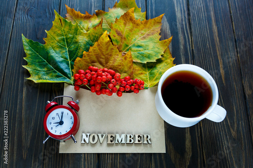 Foto op Canvas Bloemen Autumn composition with envelope and leaves, berries in it next to word October by letters, red clock and cup of coffee or hot tea. Autumn, season change concept