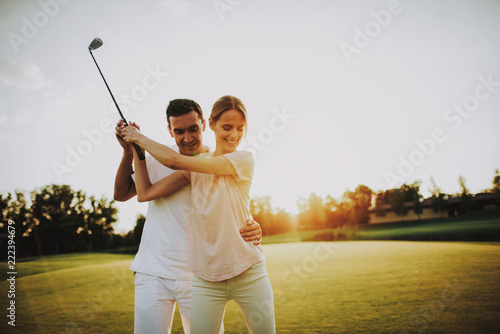 Fotografia  Young Happy Couple Playing Golf on Field in Summer