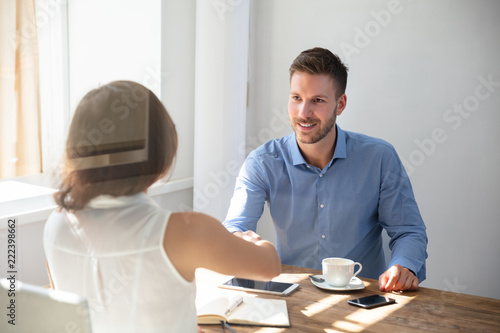 Valokuva  Two Businesspeople Shaking Hands Over Wooden Desk