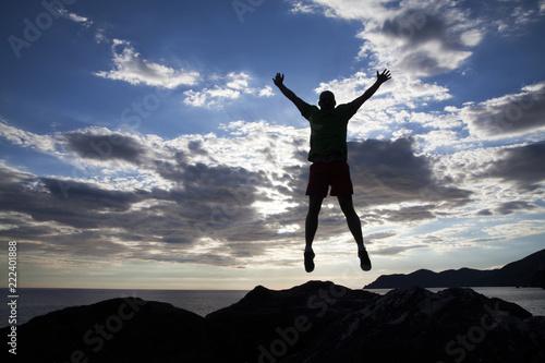 Fototapeta Man jumping on cliffs in sunset obraz na płótnie