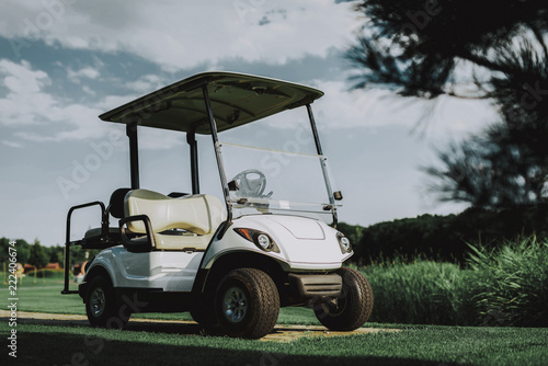 White Little Cart on Golf Field in Sunny Day.
